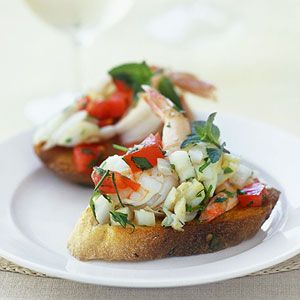 Thinly slice a baguette-style French bread loaf for these bruschetta (broo-SHEH-tah) appetizers. Toast the bread slices and top with a mixture of crabmeat, shrimp, and tomatoes tossed in a lemony herb and garlic sauce.