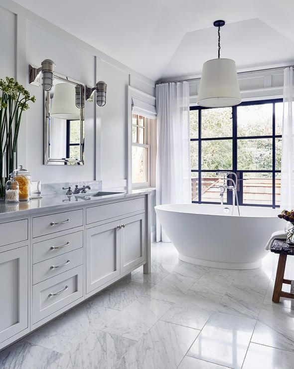 White cottage bedroom features a white double washstand topped with marble fitted with his and her sinks placed under inset framed medicine cabinets illuminated by cage wall sconces lining a wall clad in floor to ceiling board and batten trim.