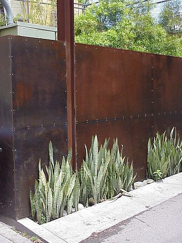 """A steel fence for an industrial-minded homeowner. Much more effective than a """"beware of dog"""" sign."""