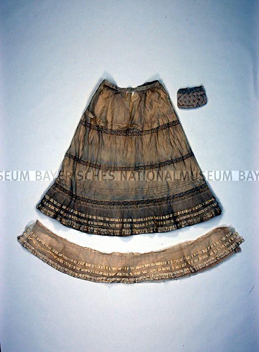 Unterrock mit Spitze, Tüll und Satinbändern  Oberstoff:  Seide (beigefarben) / genäht (maschinell) / genäht (manuell) / Baumwolle / Spitze (maschinell) / Baumwolle / Tüll  Saumfutter und Zwischenfutter:  Baumwolle  Maße: Länge 96 cm / Umfang (Taille) (ca.) 69 cm / Weite (Saum) (ca.) 286 cm  Inventarnummer: 2005/240  Fotonummer: D26968  Bayerisches Nationalmuseum