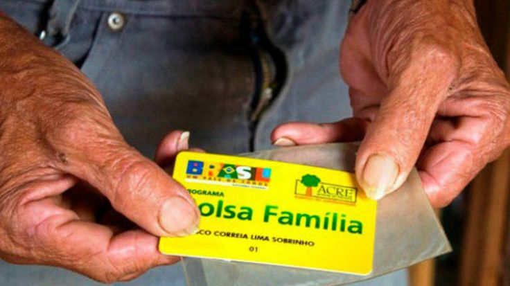 Idoso segura cartão do Bolsa Família