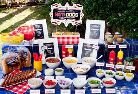 hot dog bar includes toppings like banana peppers, onions, cheese, chili, jalapenos, pickles, mayo, green onions, salsa, cole slaw, ketchup and mustard