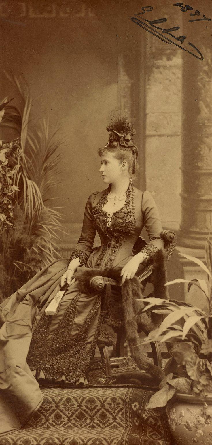 """Grã-duquesa Elisabeth Feodorovna em 1887. Ela está sentada em uma cadeira de madeira com a cabeça voltada para a esquerda e está segurando um ventoinha em sua mão direita. Ela está usando um vestido embelezado com missangas e há um longo cachecol de pele caída sobre o braço da cadeira. Há plantas para cada lado dela e um cenário pintado por trás. A fotografia é assinada e datada """"Ella 1887 'no canto superior direito."""