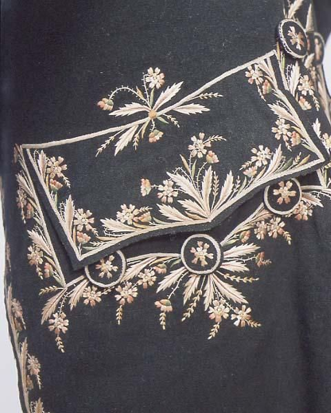 Detail pocket flap, frock coat, England, 1770-1780. Very dark green facecloth with coloured embroidery in satin stitch in a leaf and flower design down fronts and at pockets, cuffs and vent, fabric covered and embroidered buttons.