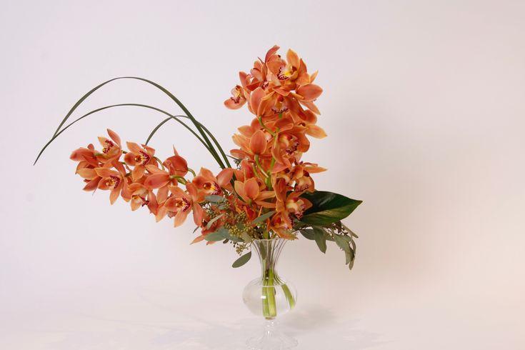 Orange mini cymbidium stems arrangement in a clear vase