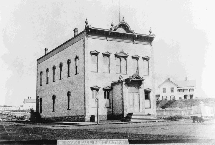 https://flic.kr/p/rmVwdk | Port Arthur Town Hall | Dates: c. 1880s Description: Port Arthur's Town Hall, on Court Street at Red River Road was not a government building at all. It was a business providing entertainment such as plays, concerts, recitations, operas and so forth, and it could be rented for meetings. When it burned to the ground early in the 20th century, many were nostalgic but few lamented it passing. They eagerly awaited the construction of a new hall that, unfortunately…