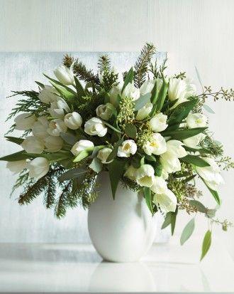 Volle vaas met witte tulpen afgewisseld met groen.