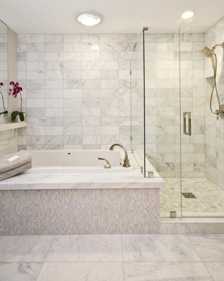 A spa tub sits next to a free standing shower in this contemporary bathroom. The marble tile adds style that flows throughout the space.
