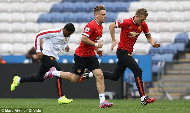 Shaw (centre) has been injured, but was pictured warming down after United's loss to Leice...