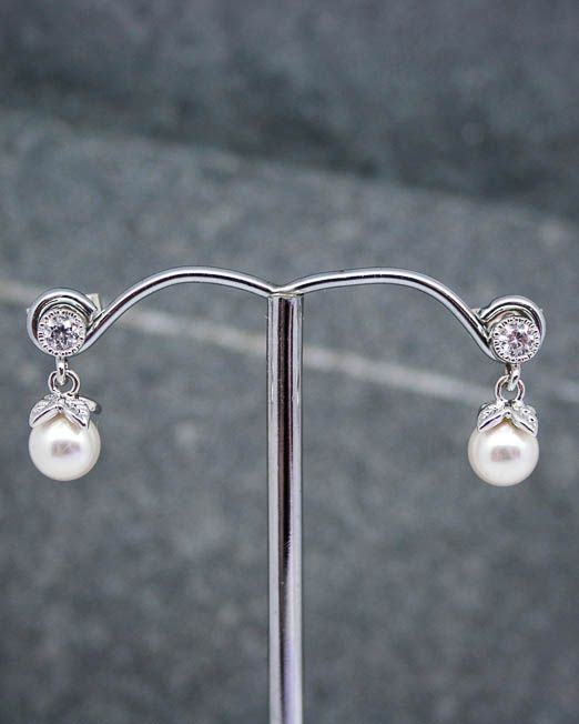 A delicate pair of cz and swarovski pearl stud earrings.  The swarovski pearls measure 6mm and the cubic zirconia 4mm making the total drop 15mm approx.  They are set into rhodium plated fittings with 925 silver posts and scrolls.  #Crystal #Earrings #Pearl #Portside