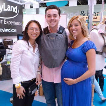 Ray Quinn & his wife Emma with Sheena Woods, trying on the MaByLand Trek Snuggle Carrier at the Baby Show!