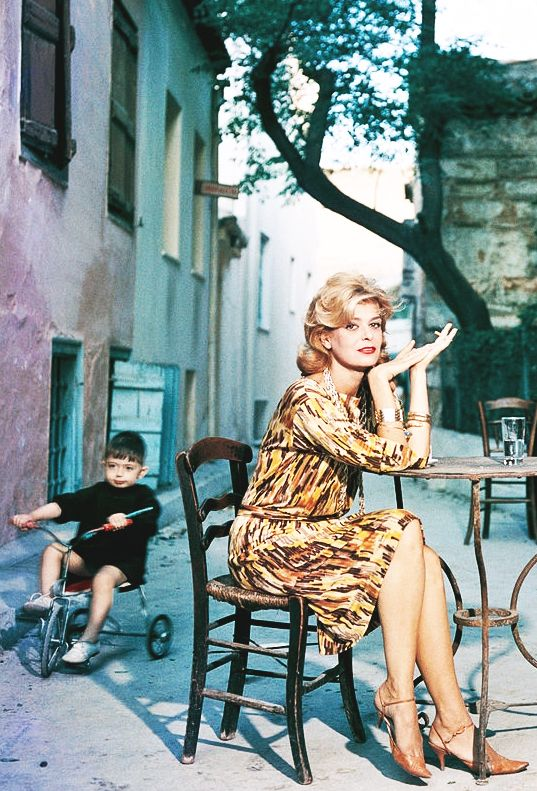 Melina Mercouri sitting at a street cafe in Athens, photographed by Slim Aarons.