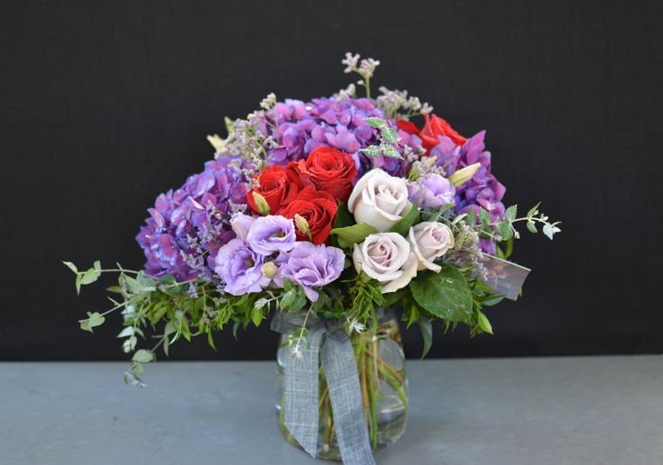 Beautiful hydrangea, roses and lisianthus flower arrangement in a clear glass vase
