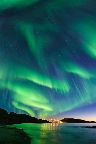 "Aurora Borealis in Ersfjord, Norway.  During the Northern Hemisphere's autumn and spring, solar magnetic fields are oriented in just the right way to cause ""rips"" in Earth's magnetic field. The resulting increase in solar wind on Earth encourages auroral sky shows but can also damage satellite technology and electrical grids on the ground. (National Geographic)"