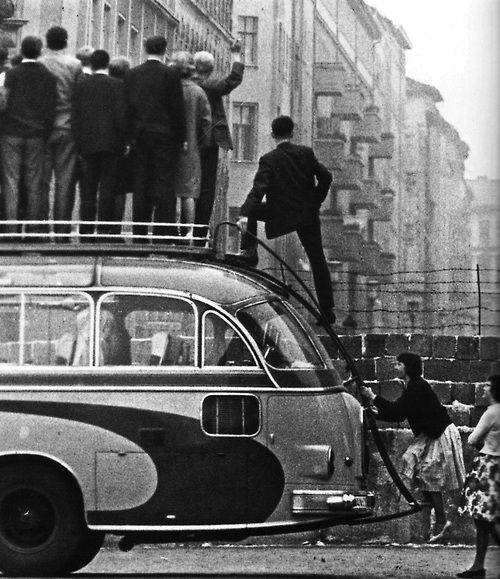 Sightseers climb atop a tour bus to look over the newly built Berlin Wall, 1961