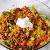DORITOS TACO SALAD -- 1 lb. ground beef 1 head iceberg lettuce, cleaned and torn into bite site pieces 1 envelope of taco seasoning 1 medium sized tomato, diced 1 bag of nacho Doritos 1 bottle French Dressing 1 ½ cup shredded cheddar cheese