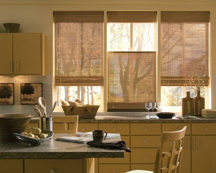 store en bambou enrouleur dans la cuisine aménagée avec des meubles en bois clair et plans de travail en granit
