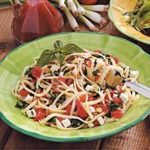 "Spinach Tomato Linguine Recipe -Chock-full of garden freshness, this colorful toss makes an excellent side dish or meatless entree. ""Sometime I substitute penne pasta and add cooked chicken for a heartier main meal,"" says Rosemary Averkamp of Genoa, Wisconsin. ""Using garlic-flavored feta cheese is a great touch."""