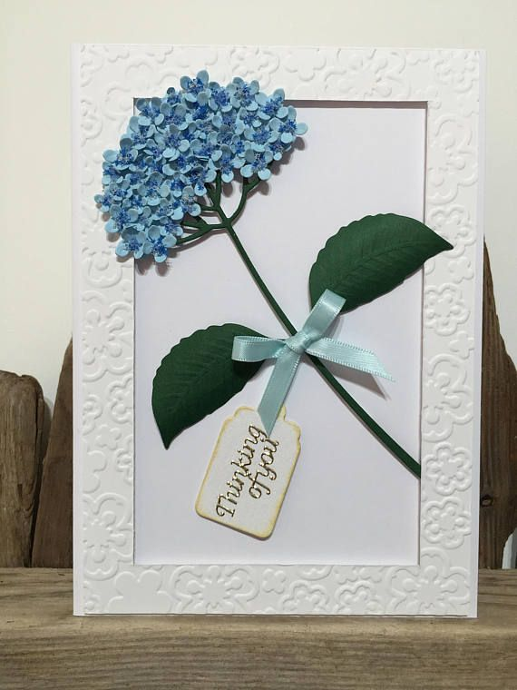 Lovely hand-crafted Thinking Of You card featuring a Blue Hydrangea flower mounted within an embossed frame.  Blue cardstock forms the Hydrangea, die cut using the Impression Obsession Hydrangea die. The centres of each flower have been adorned with Flower Soft in Delphinium Blue colour. The leaves have been cut from green cardstock and gently shaped and embossed, highlighting the veins.  Spellbinders M-Bossabilities EL-020 Awesome Blossoms Embossing Folder has been used to create the frame…
