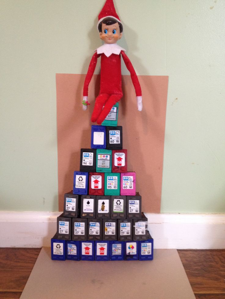 Elf on the Shelf hiding atop a Christmas tree made from used HP ink cartridges.  Please remember to recycle your used ink cartridges!