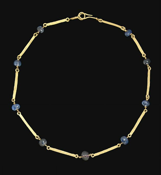 A ROMAN GOLD AND SAPPHIRE NECKLACE   CIRCA 2ND-3RD CENTURY A.D.   Composed of lentoid sapphire beads interspersed with gold bars with rounded pierced terminals at either end, modern hook and loop closure