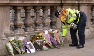A police officer lays flowers on Whitehall around a photograph of police officer Keith Palmer who was killed in the March 22 terror attack in Westminster