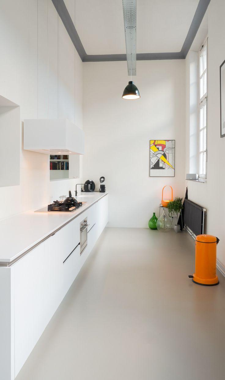 Langwerpige witte keuken in oude gang van school. Perfecte plek voor de keuken door de smallere breedte. De hoogte van 4.5m geeft veel lucht aan deze ruimte. De kozijnen rechts zijn noord georiënteerd en geven d perfecte lichtinval.