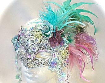 Esta máscara de la mascarada veneciana delicado es turquesa y lila con tono mano teñido superposiciones de encaje y abundancia de la chispa! La mascarilla moldeada lentejuelas ha sido cuidadosamente con incrustaciones de perlas, perlas y diamantes de imitación y tiene penachos de plumas de avestruz, biot y marabú. Rosas de seda con cuentas en la corona del este de una creación buena y la máscara de lazos con cintas de organdí en la espalda. Tiene un renacimiento muy sienten a la misma y es…