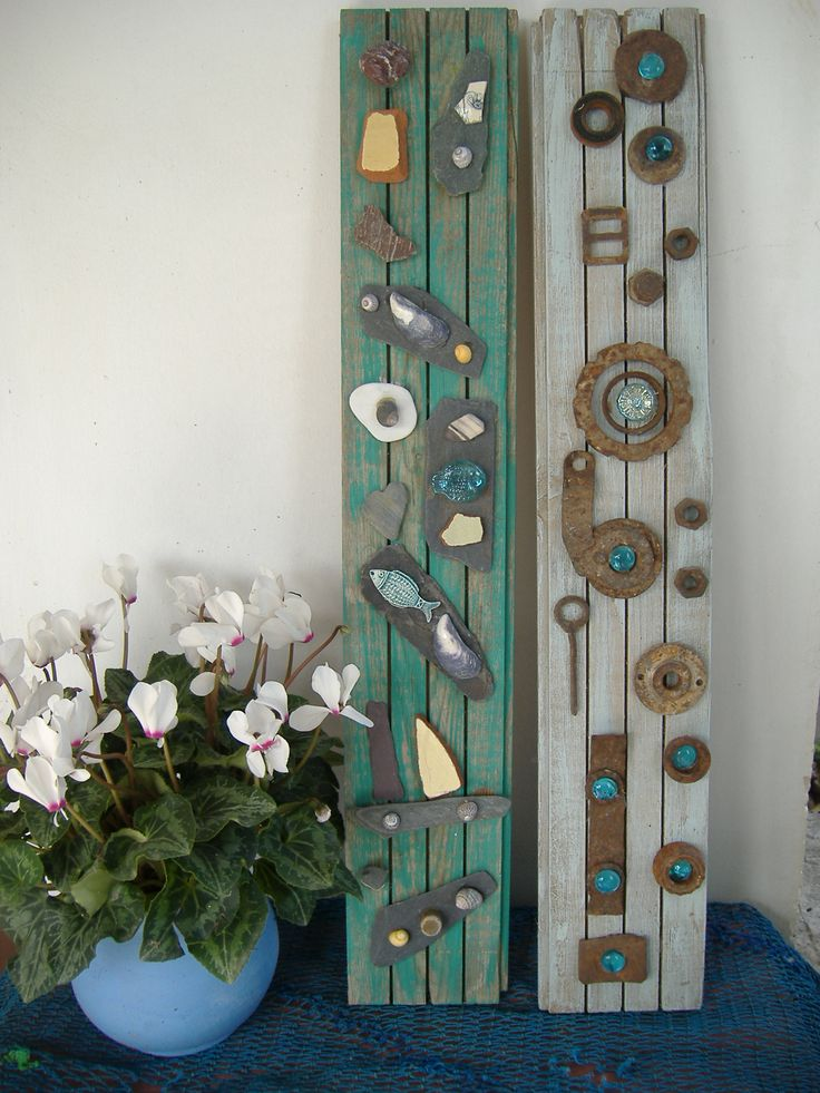 Upcycling old floor boards, decorated with Shells, slate, sea pottery, pebbles and metal and glass. Sea side art design by Philippa komercharo.