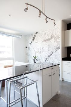 """Unusually, there is seating on both sides of this kitchen island, while clear """"stools from CB2 allow the light from the floor-to-ceiling windows to pass through and fill the kitchen.""""  Kitchen Island Breakfast Bar Ideas & Inspiration   Apartment Therapy"""