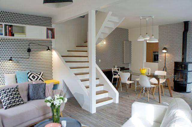 Peint en blanc, l'escalier imposant occupe une place de choix dans le séjour