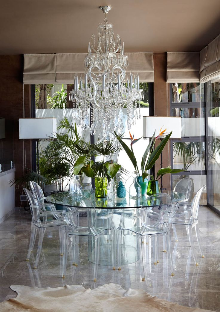 """Crystal and glass dining room with """"ghost"""" chairs and greenery in background"""