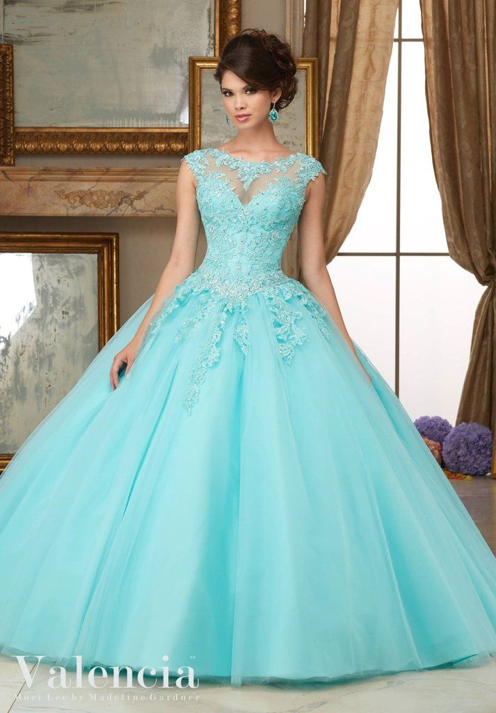 Full of amazing details, you'll look like a beautiful Princess wearing Mori Lee Mori Lee Valencia Quinceanera Dress Style 60006 at your Sweet 15 party. Made out of lace and tulle, this ball gown features a cap sleeve lace bodice decorated with crystal beading, sheer illusion neckline, long A-line skirt, and a lace-up corset back. A matching stole is included.  Colors: Aqua, Scarlet Red, Blush, White  Please allow 4 - 5 months for delivery because Mori Lee Valencia Quinceanera dresses are…