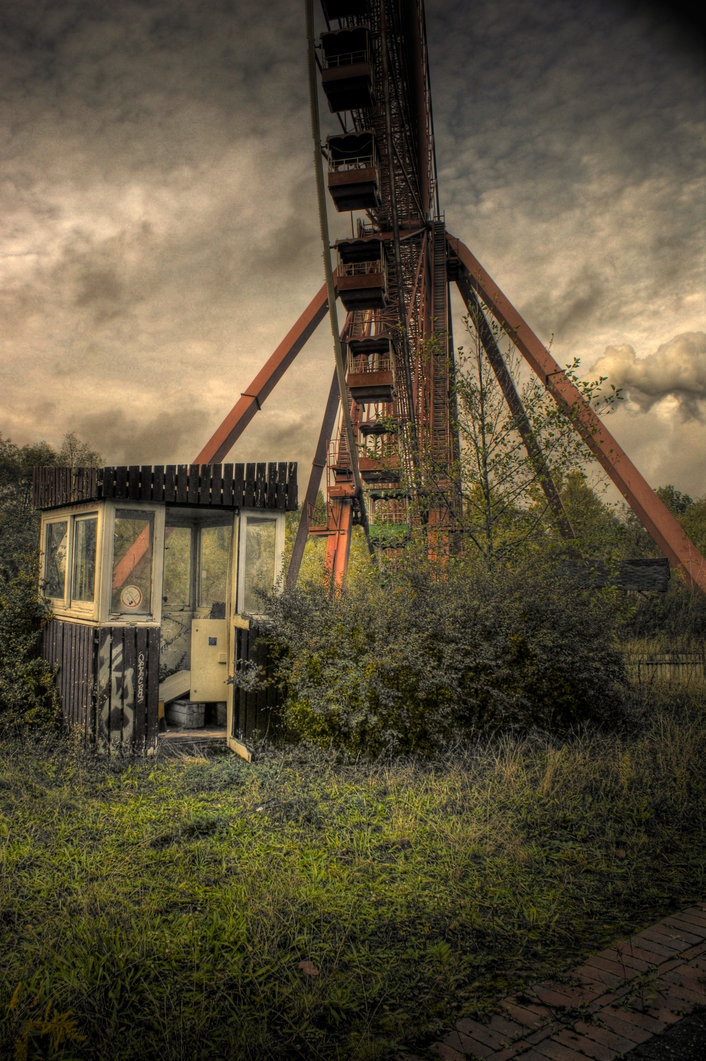 overgrown and abandoned ferris wheel with ticket kiosk