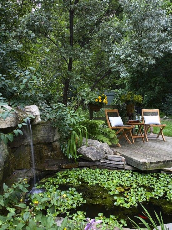 Relaxing retreat on a deck next to lily pond with koi fish, and the trickle of a  small waterfall