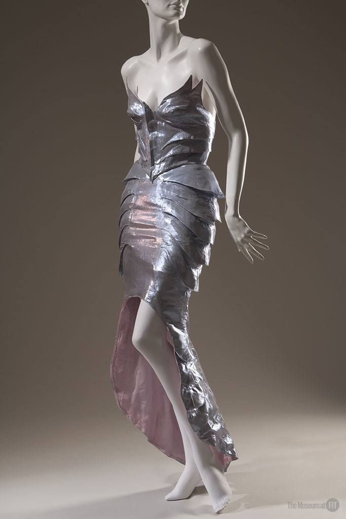 """Thierry Mugler ensemble, spring 1989. #FairyTaleFashion via the #MuseumatFIT  This two-piece """"mermaid"""" dress, with its precise, figure-enhancing tucks of fabric, underscores Thierry Mugler's ability to combine fantasy with adept craftsmanship. In 1988, Mugler created a """"fairy tale kingdom"""" for the presentation of a collection devoted to the lost city of Atlantis. Mermaids, sea nymphs, sharks, and starfish graced the catwalk."""