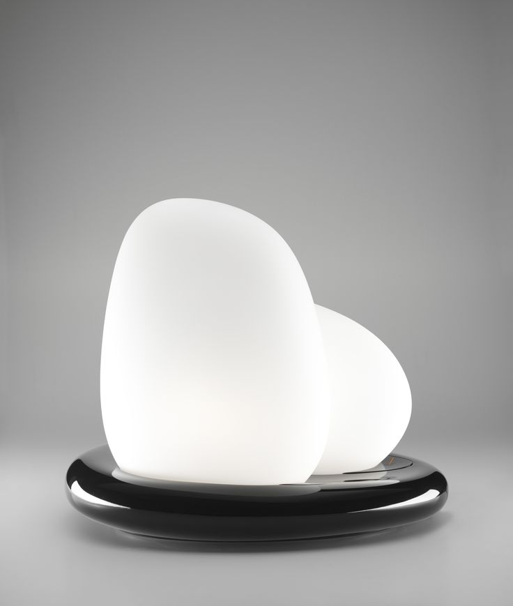 Moai design by Defne Koz for Leucos. Of sculptural Polynesian inspiration, Moai is a floor/table lamp consisting of two large scale diffusers of white satin blown glass. Base of dense resin with bright white or bright black finishing. Double switching lamp.