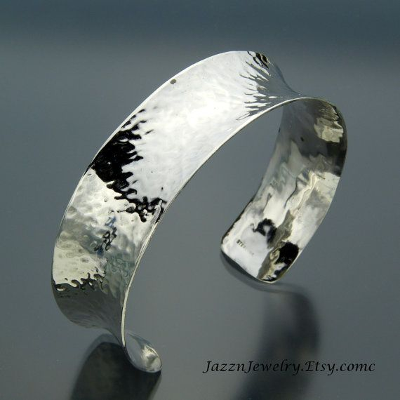This minimalist hammered cuff has a distinctive concave shape to set it apart and make it special. After being hammer forged with a dimple texture, it is formed into a saddle shape. This shape is very comfortable to wear.    It has a mirror polish inside and out. The facets of the dimples catch and flash bright sparkly light. This is a great bracelet that goes well with any outfit, from jeans, office wear or evening wear. Its one of those go to pieces of jewelry that pops on and is always a…
