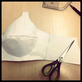 Lesson 6 : Drafting Basic Bra Patterns  Today we learned how to draft basic bra patterns, using an MS20 size 34B bra wire as a starting point. After much precise measuring and drawing we were asked to pin our patterns together to see them 3-dimensionally and then alter them to make them more aesthetically pleasing by cutting into them