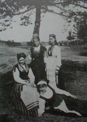 """""""Osa keisarinnan veneen soutajia Lappeenrannassa 1885. Edessä on Ida Aalberg """"hämäläispuvussa"""", istumassa Lapväärtin puvussa Mustasaaren rovastin tytär Emmy Cannelin, takana pohjoissavolaisessa puvussa kuopiolainen virkamiehen tytär Alma Ahnger ja Karjalan edustajana talollisentytär Lydia Haaranen Tohmajärveltä Äyräpään kihlakunnan puvussa, jossa esiliina on sidottu epätavallisesti kostulin päälle."""""""