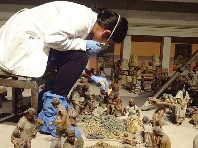 Especialista del INAH restaurando la maqueta del Mercado de Tlatelolco