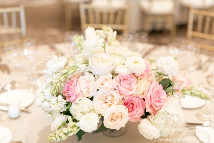 elegant and traditional large low centerpieces overflowing with white, ivory and pink roses, white hydrangea, blush garden roses, tuberose, and white ranunculus in footed mercury glass compotes