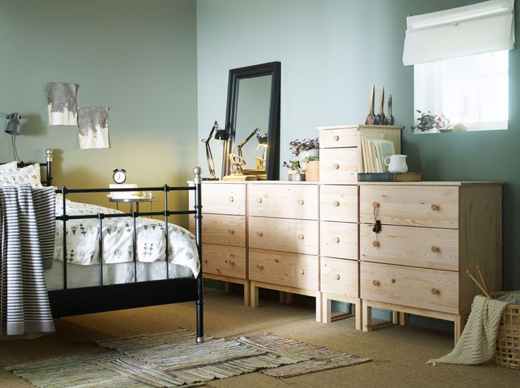 A bedroom with a large black iron bed shown together with solid pine chest of drawers in different sizes and a black mirror.