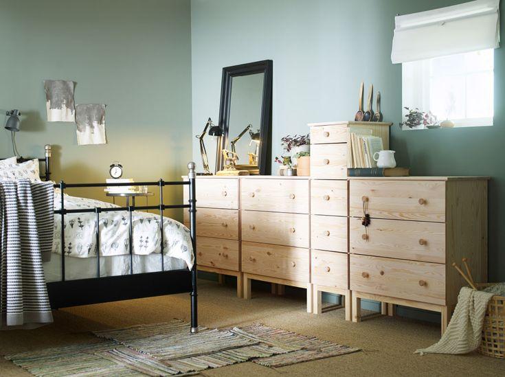Quarto com uma cama grande em ferro preto, mostrada em conjunto com cómodas em pinho maciço de vários tamanhos e um espelho em preto