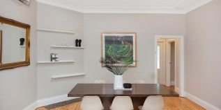 Dining area, high patterned ceiling, table setting, skylight, fern, wall art, shelves, mirror