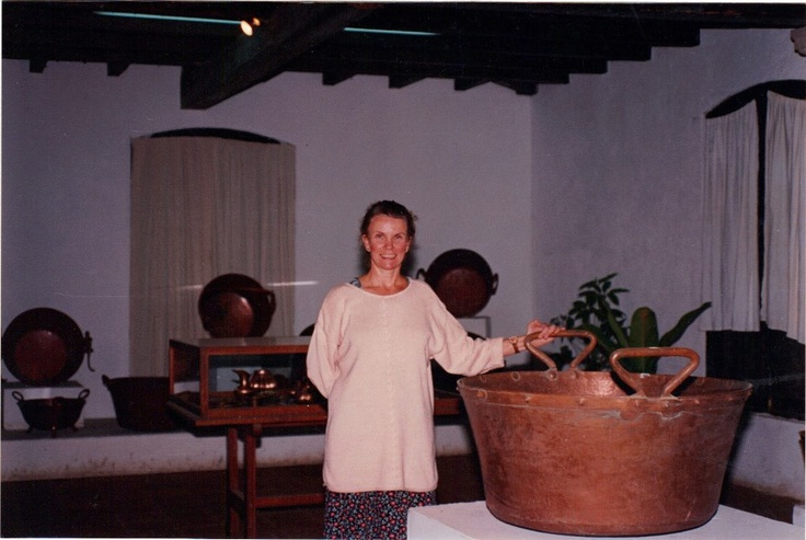 """The third week of every August since the late 1940's our village Santa Clara del Cobre hosts a """"Concourso"""" (contest) and many of the coppersmiths submit a masterpiece hoping to win a prize and recognition for their talent. This picture was taken several years ago during the Concourso and I'm standing by a sample of a large cazo (handled bowl), a design that has become the village's signature piece"""