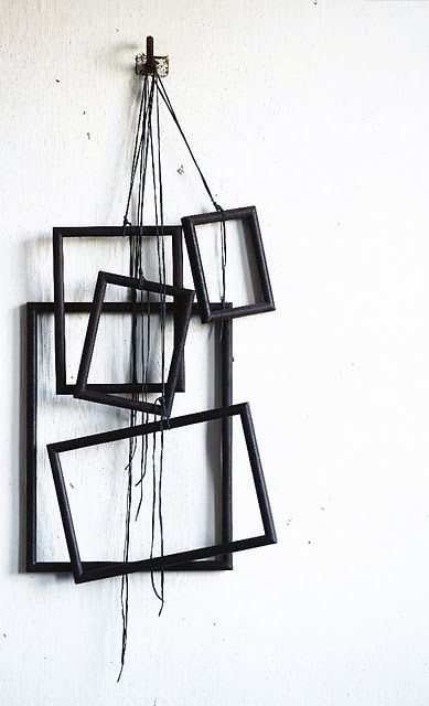A bunch of old picture frames painted black can make a striking work of art when hung together with some rope.