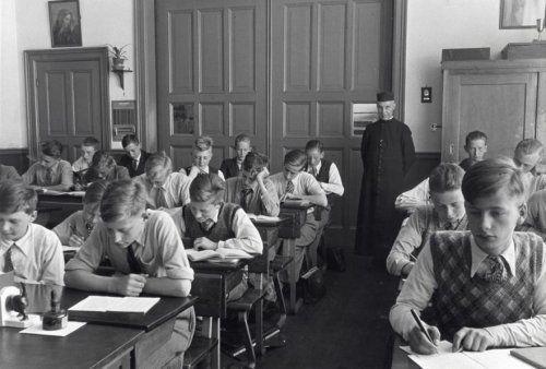 Onderwijs op katholieke school. Jongens/leerlingen in schoolbanken in de klas, met geestelijke (broeder Theodorus) als onderwijzer. [1936].