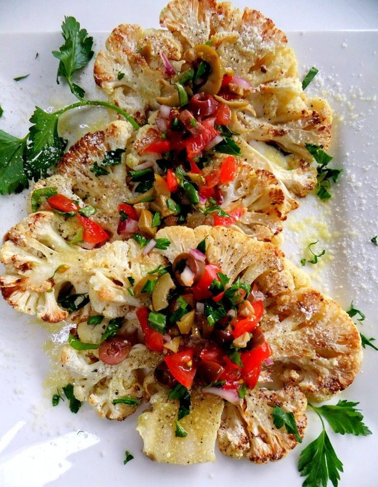 """cauliflower """"steaks"""" topped with grape tomatoes, green and kalamata olives, red onion, basil, + parsley"""