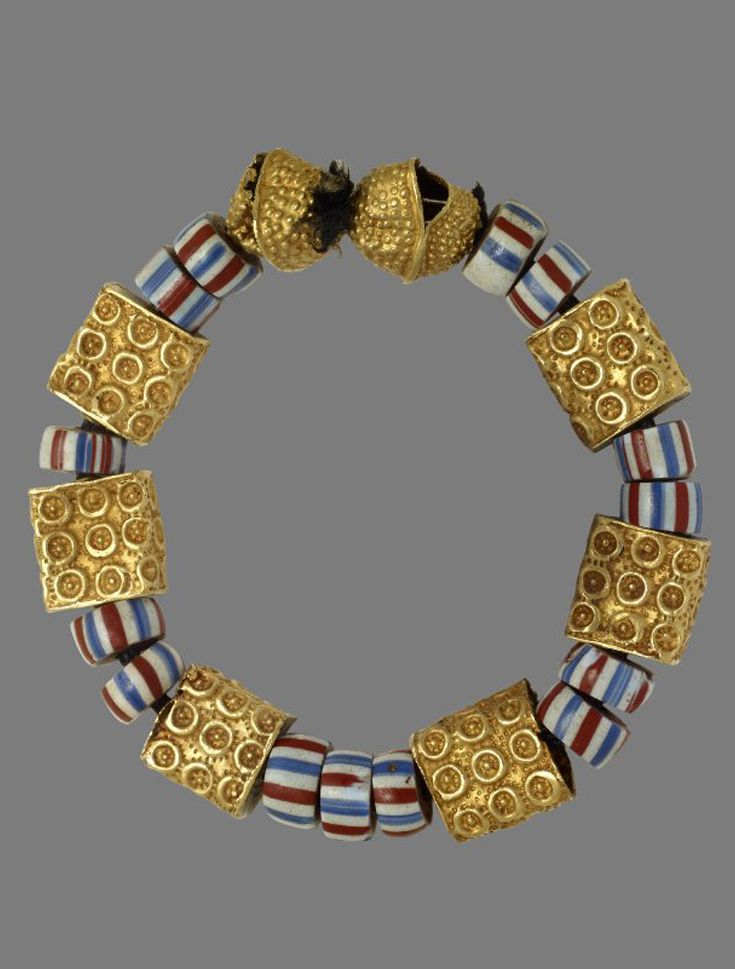 Africa | Bracelet / amulet (suman) composed of 8 lost wax cast gold beads which alternate with fourteen glass beads decorated with red, white and blue horizontal stripes. | Asante people, Ghana. | 19th - early 20th century || {6.8}